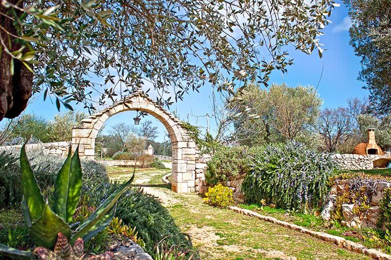 Portale in pietra tradizionale pugliese di ingesso al giardino con siepe di rosmarino